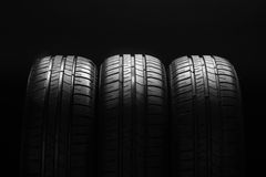 Gomme di automobile economiche in consumo di carburante di estate su fondo nero Fotografia Stock