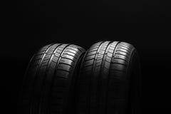 Gomme di automobile economiche in consumo di carburante di estate su fondo nero Fotografie Stock