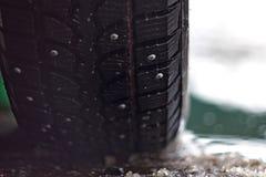 Gomme fissate nella neve bagnata di primavera contro il contesto di acqua fotografie stock libere da diritti
