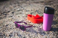 Gomme gymnastique, tasse thermo et verres sur le sable photo libre de droits