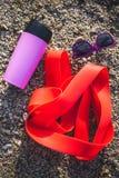 Gomme gymnastique, tasse thermo et verres sur le sable photos stock