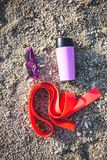 Gomme gymnastique, tasse thermo et verres sur le sable images libres de droits