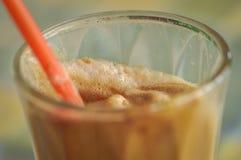 ?gonblicklig coffe i ett exponeringsglas med ett r?tt sugr?r arkivfoto
