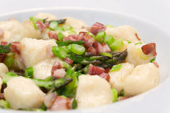 Goncchi with asparagus and bacon. Close up of handmade gnocchi with bacon and asparagus Royalty Free Stock Images