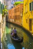 Gondel schwimmt auf den Kanal unter den hellen Häusern Stockfotografie