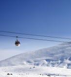 Gondelbahn und Ski neigen sich am schönen Sonnentag Stockfotografie