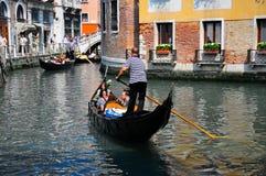 Gondelier die een gondel navigeert door kanaal Royalty-vrije Stock Foto's