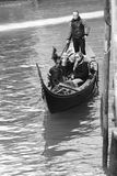 Gondelier dragende toeristen in zwart-wit Venetië, Stock Afbeeldingen
