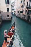 Gondelier met gondel door groene kanaalwateren van Venetië Italië stock foto's