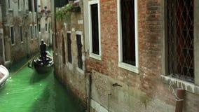 Gondelierzeilen langs één van de Venetiaanse kanalen stock footage