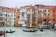 Gondeln, die durch Wasserkanal in Venedig segeln Stockfotografie