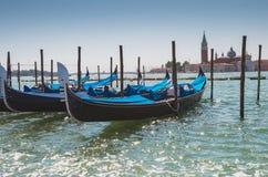 Gondels aan de polen op Kanaal in Venetië worden gedokt dat stock afbeeldingen