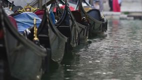 Gondels in rij worden geparkeerd, die op water, retro taxi voor toeristen in Venetië schommelen dat stock video