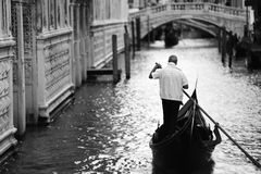 Gondiler in Venice, black and white picture. Gondola with gondolier on a channel in Venice, Italy Stock Photo