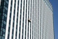 Gondol med fönsterrengöringsmedel på skyskrapa Royaltyfri Bild