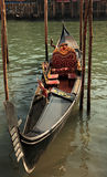 Gondola. A gondola parked on a Venetian canale between wooden poles Stock Images