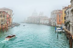 Gondola on Canal Grande with Basilica di Santa Maria della Salute in the background, Venice, Italy. Foggy misty Venice. Canal channel, historical, old houses and royalty free stock photography