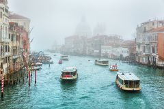 Gondola on Canal Grande with Basilica di Santa Maria della Salute in the background, Venice, Italy. Foggy misty Venice. Canal channel, historical, old houses and stock images