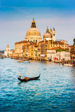 Gondola on Canal Grande with Basilica di Santa Maria della Salute at sunset, Venice, Italy Stock Image