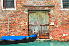 Gondola on canal and old brick house in Venice, Italy. Stock Photos