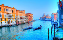Gondola on canal, Venice - Italy. Beautiful view over the famous Grand Canal illuminated in sunset light, and gondolier transporting tourists by gondola, in Stock Image