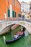 Gondola carrying tourists under a bridge on a narrow canal in Venice Stock Image