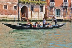 Gondola with cheerful girls as passengers on the Grand Canal, Venice, Italy. Royalty Free Stock Image