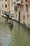 Gondola crossing a small canal Stock Photos