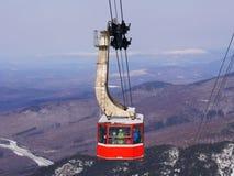 Gondola dello sci e fondo ammucchiati delle montagne della neve Immagine Stock