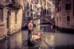 Gondola floats along old narrow street in Venice Royalty Free Stock Photography