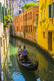 Gondola floats on the channel among the bright houses Stock Photography