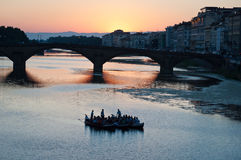 Gondola in Florence. On river Arno in Florence gondola full of people with bridge alla  Canaria behind and beautiful soft sunset Royalty Free Stock Photos