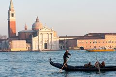 Gondola in front of San Giorgio Maggiore Church in Venice lagoon, Italy. Gondolier rowing a gondola in front of San Giorgio Maggiore church seen across the water royalty free stock images