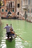 Gondola with gondolier on a canal in Venice, Italy Royalty Free Stock Photos
