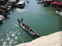 Gondola with a gondolier and passengers in Venice. Royalty Free Stock Photos
