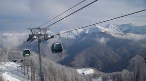 Gondola lift against mountain range. Gondola lift against panoramic vew of mountain range Royalty Free Stock Images