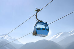 Gondola lift in the ski resort. In the early morning at dawn with view of mountain ski slopes and peaks Royalty Free Stock Images