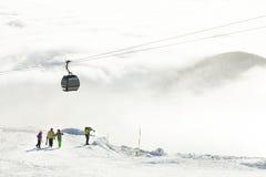 Gondola moderna che va sulla montagna ad un'area di località di soggiorno degli sport invernali un giorno nuvoloso Fotografia Stock Libera da Diritti
