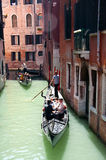Gondola in the morning. Two traditional boats gondolas with gondoliers and people on board moving through narrow canals - Venice, Italy, 18 May 2012 Royalty Free Stock Photography