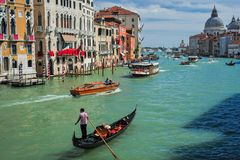 Gondola and Boats on the Grand Canal. A gondola moves along the Grand Canal, Venice, Italy Royalty Free Stock Image