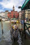 Gondola Near the Rialto Bridge. Venice, Italy- July 28,2011:  A gondola with tourists at a dock near the Rialto Bridge in Venice Stock Photography
