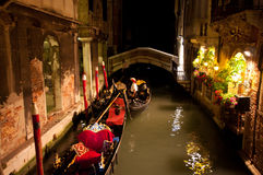 Gondola at night. Venetian gondolier lays up his gondola in one of water canals at a night time against cityscape of old buildings and illumination - 17 May 2012 Stock Images