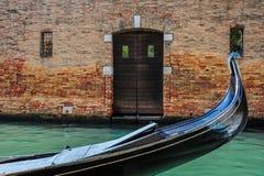 Gondola Outside a Home in Venice. A gondola rests outside of canal-side residence in Venice, Italy Stock Photo