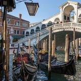 Gondola parking near the famous Realto bridge on a Grand Canal in Venice with the Servizio Gondole sign. Venice, Italy - March 21, 2018: Gondola parking near the stock image