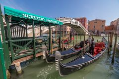 Gondola parking near the famous Realto bridge on a Grand Canal in Venice with the Servizio Gondole sign. Venice, Italy - March 23, 2018: Gondola parking near the stock photos