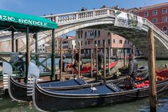 Gondola parking near the famous Realto bridge on a Grand Canal in Venice with the Servizio Gondole sign. Venice, Italy - March 23, 2018: Gondola parking near the royalty free stock images
