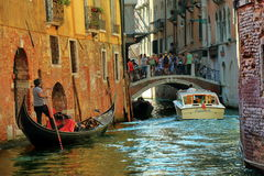 Gondola with passengers and motorboat near the old bridge. Venice, Italy - August 21, 2015: Gondola with passengers and motorboat near the old bridge with royalty free stock photos