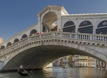 A gondola passes under the Rialto Bridge of Venice, Italy Royalty Free Stock Images