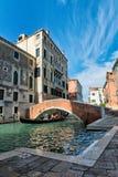 Gondola passing under a bridge in Venice Stock Photos