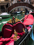 Gondola with Red Seat and Golden Decoration in Typical Canal in Stock Photos